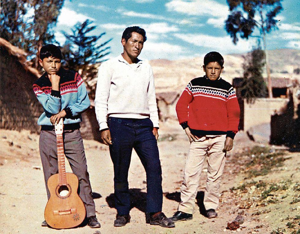 Manuelcha a los 12 años, con su primera guitarra. Lo acompañan su tío Moisés y su hermano Percy. [Foto: archivo familiar]